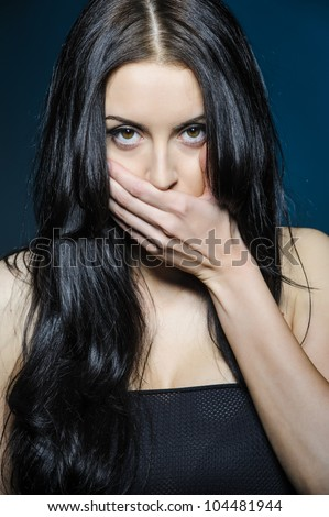 Beautiful girl covers her mouth with his hand - stock photo