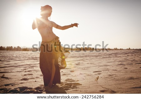 Beautiful girl dancing ethnic dances in desert - stock photo