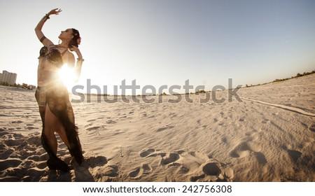 Beautiful girl dancing ethnic dances in desert - stock photo