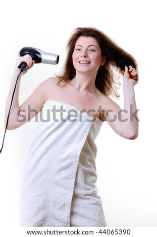beautiful girl doing her hair with a hairdryer