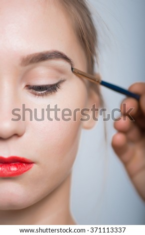 Beautiful girl doing make-up, eye color brush, clean skin isolated on background