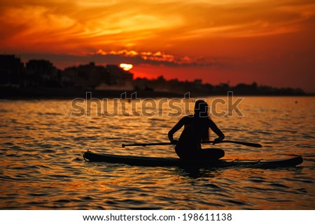 Beautiful girl doing yoga meditation on the paddle surf board accompanied by a stunning sunset