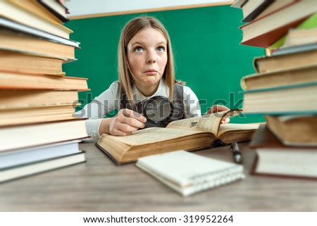 Beautiful girl doubts about read / photo of teen school girl wearing glasses, creative concept with Back to school theme - stock photo
