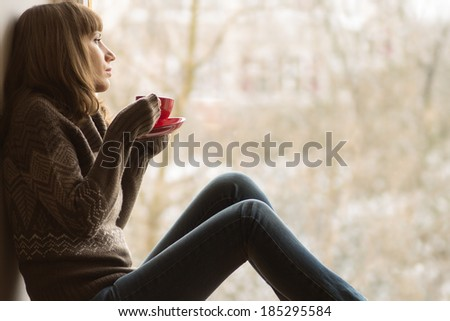 Beautiful girl dreaming with cup of coffee or tea near window - stock photo
