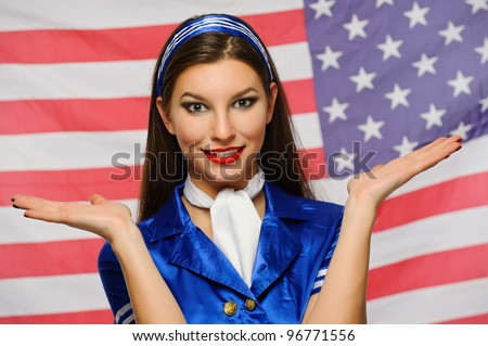 beautiful girl dressed as a stewardess on the background of the American flag with their hands
