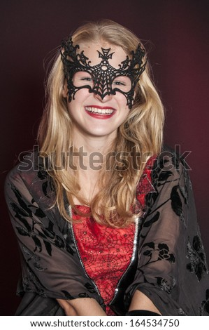 beautiful girl dressed as Halloween devil witch isolated on dark background