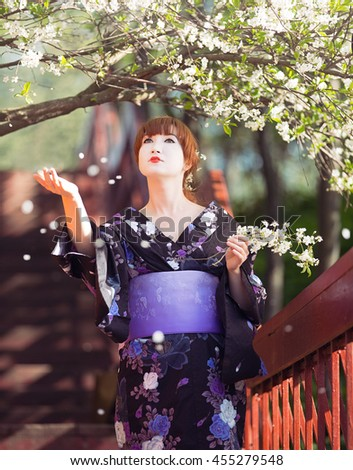beautiful girl dressed in a kimono and a pear-like standing under cherry blossom - stock photo
