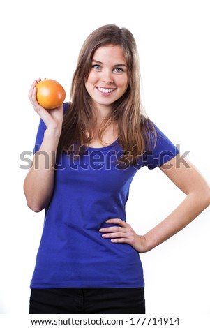 Beautiful girl dressed in blue t-shirt and holding orange - stock photo
