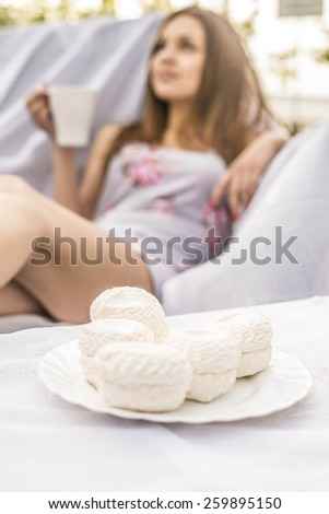 Beautiful girl drink coffee or tea outdoor on green spring park background Young adult woman enjoying and eat unhealthy food snack in lunch break smiling happy.White cakes - zephyr in focus - stock photo