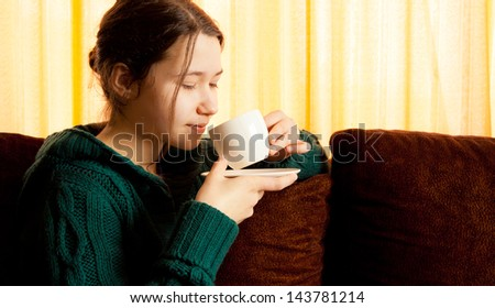 Beautiful girl drinking coffee at home - stock photo