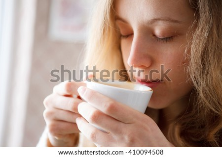 Beautiful girl drinking coffee. Cup of hot beverage. Coffee-break - stock photo