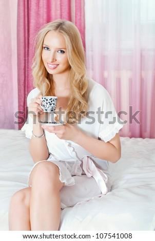 Beautiful girl drinking coffee in bed - stock photo