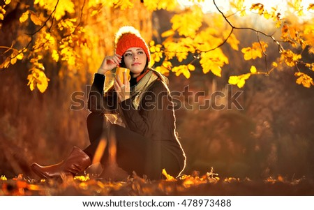 Beautiful girl drinking coffee on an autumn background
