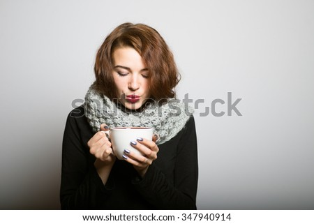beautiful girl drinking coffee or tea to keep warm in the winter, the office manager concept shot isolated on gray background - stock photo