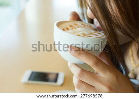 beautiful girl drinking hot coffee or tea in coffee cafe, model asia women, female of thai people - stock photo