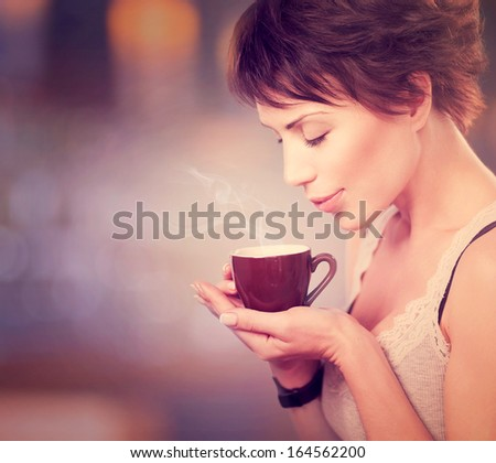 Beautiful Girl Drinking Tea or Coffee. Beauty Woman with Cup of Hot Beverage. Enjoying Coffee. Warm Pastel Colors  - stock photo