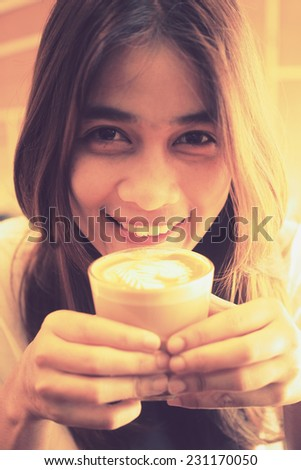 Beautiful Girl Drinking Tea or Coffee in vintage color toned style - stock photo
