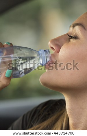 Beautiful Girl drinks fizzy water from clear plastic bottle