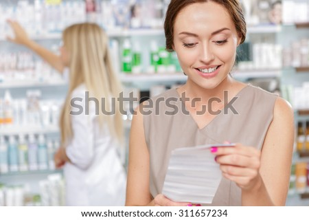 Beautiful girl druggist helping a customer - stock photo