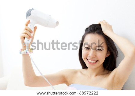 Beautiful girl drying her hair with hairdryer