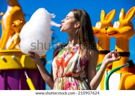 Beautiful girl eating cotton candy at an amusement park - stock photo
