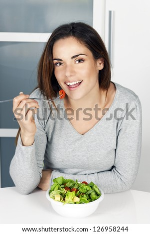 beautiful girl eating healthy food at home - stock photo