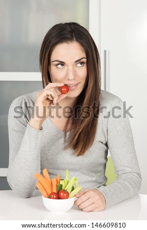 Beautiful girl eating vegetables food at home - stock photo