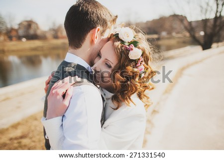 beautiful girl embraces guy. woman and man in love. happy wedding couple. bride and groom hugs outdoors in park. happy young people - stock photo