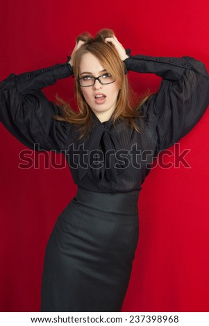 Beautiful girl emotion screaming. Bespectacled sensual surprise girl on a red background. - stock photo