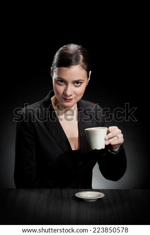 beautiful girl enjoying a cup of coffee on dark background  - stock photo