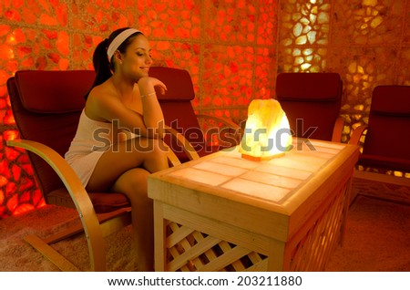Beautiful girl enjoying her therapy in salt room. - stock photo