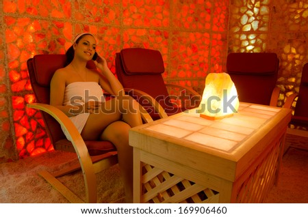 Beautiful girl enjoying her therapy in the salt room. - stock photo