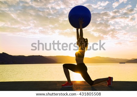 Beautiful girl exercise by the water with ball. - stock photo