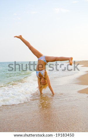 Beautiful girl exercising at sea beach