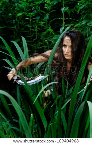 Beautiful girl explores the savage jungle in search of prey - stock photo