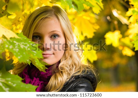 Beautiful girl face poses on a park, autumn color leaves on the background, horizon format - stock photo