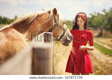 Beautiful girl feeding  her horse.