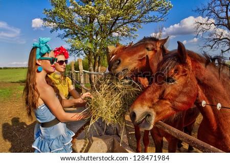 Beautiful girl feeding her horses at ranch - stock photo