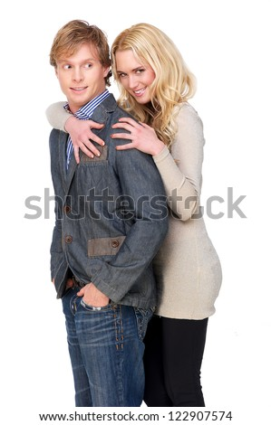 Beautiful girl flirting and embracing a nerd guy. He is looking behind with a nervous expression on his face. Opposites do attract. Isolated on white background - stock photo