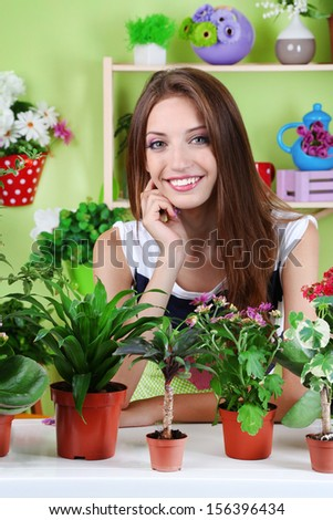 Beautiful girl florist with flowers in room - stock photo