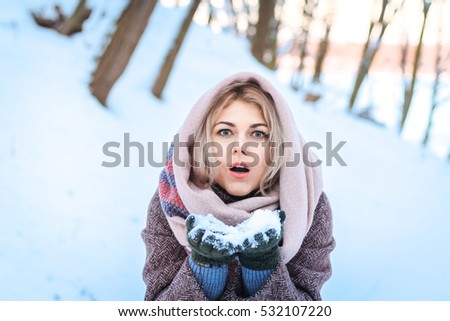Beautiful girl fun outdoor in winter forest under snowflakes.Pretty young model on blue background holding a snow. winter scene people magic.