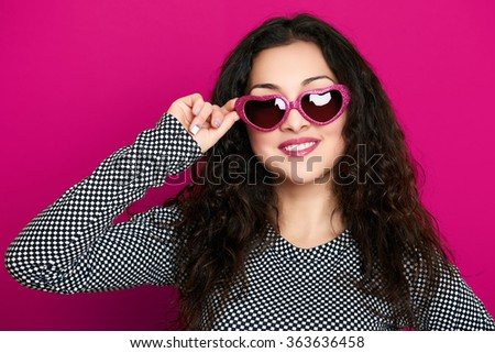 beautiful girl glamour portrait on pink background in heart shape sunglasses, long curly hair - stock photo