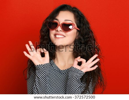 beautiful girl glamour portrait on red show okay gesture - stock photo