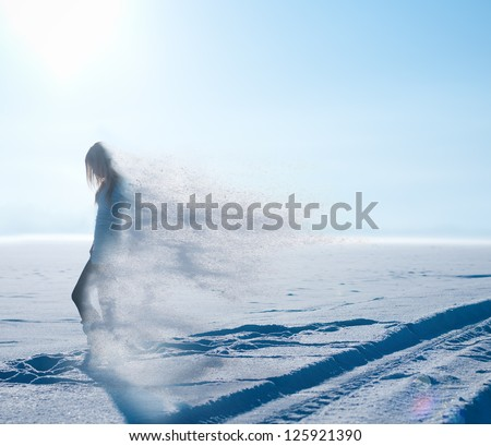 beautiful girl goes through the snowy field and shatters into snowflakes - stock photo