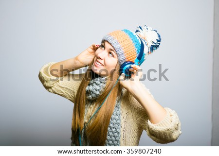 beautiful girl happy listening to music with big headphones with a phone or player, knit cap, winter concept, photo studio, portrait of a woman isolated on gray background - stock photo
