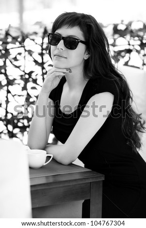 Beautiful girl having breakfast at cafe. With sun glasses. - stock photo