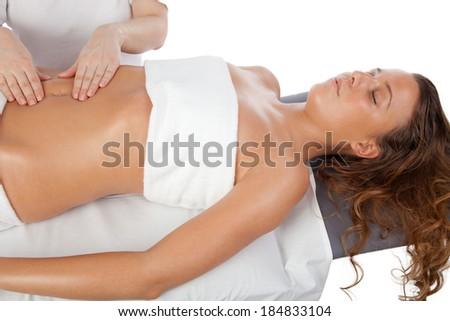 Beautiful girl having stomach massage. Body care shooting in studio - stock photo