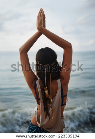 Beautiful girl hippie standing back and looking at the sea. Yoga and meeting the dawn. Tranquility and meditation. - stock photo