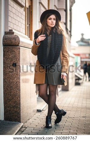 beautiful girl hipster hat walks through the city