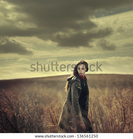 beautiful girl hipster is on the field at sunset - stock photo
